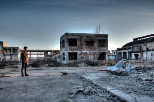 A man standing alone, looking at buildings destroyed by natural disasters