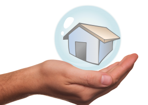 A hand holding a bubble with a small house inside it; plain, white background
