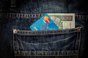 Blue jeans a with a back pocket containing a credit card and cash