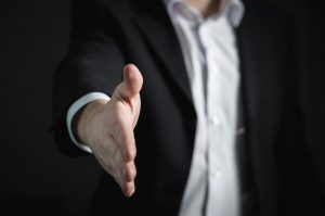 A man in a suit extending his hand offering a handshake
