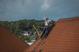 A man repairing the roof to prevent natural property damage