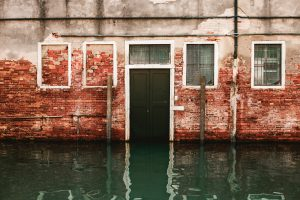 Water flooding a house as seen from the outside is one of the many causes for mold damage insurance claim