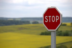 Traffic stop sign; a green field and the sky in the background - stoping people from owning a modular home