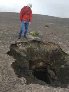 A man standing next to a hole in the ground, planning to file sinkhole damage insurance claims