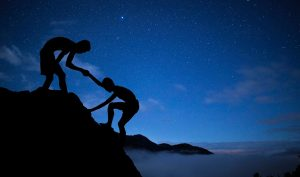 A man helping another man climb a hill, sky in the background, evening time