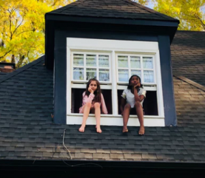 Protect your home from storms by checking the shingles on your roof, like these two girls are doing through the window panel.