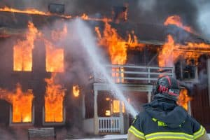 Firefighter putting out the flame in a house