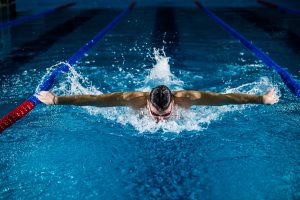 Man swimming butterfly style in an olympic-sized pool