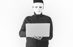 A man wearing a mask working on a laptop