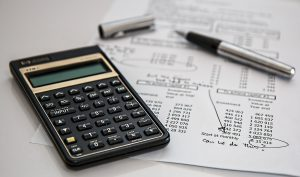 A calculator next to a bill and a pen.