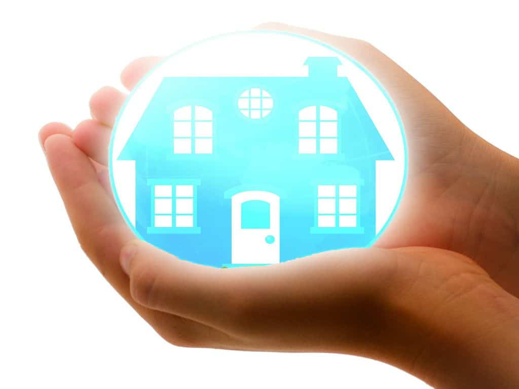 A person holding an orb containing a blue house, representing a home insurance policy.