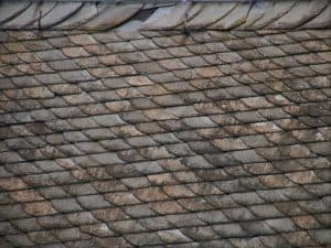 A rusty roof with completely damaged tiles.