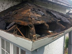 A roof with a damaged, rotten structure.