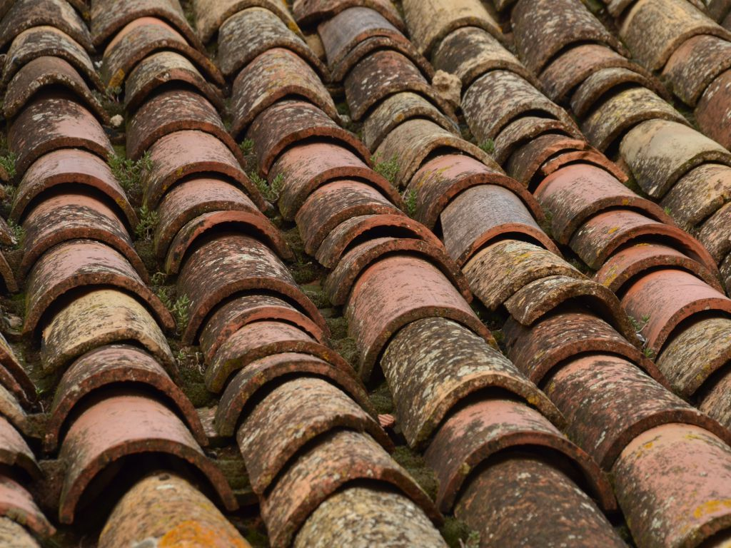A roof with badly maintained tiles, representing the dangers of a leaking roof.