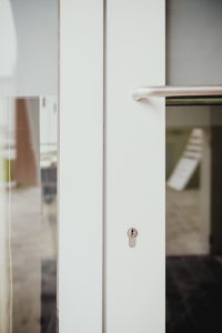 small lock on white glass doors
