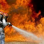 A firefighter putting out a flame, representing how to prepare for wildfires.